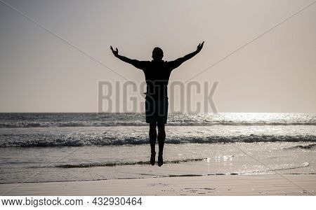 Silhouette Of Athletic Man Jumping With Raised Hands On Summer Beach, Freedom