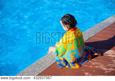 Child Is Sitting By Pool. Little Girl With Braided Pigtails Is Sitting On Side Of Pool, Looking At W