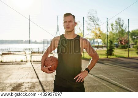 Portrait Of Handsome Male Basketball Player Looking Away While Posing With A Basketball On The Court