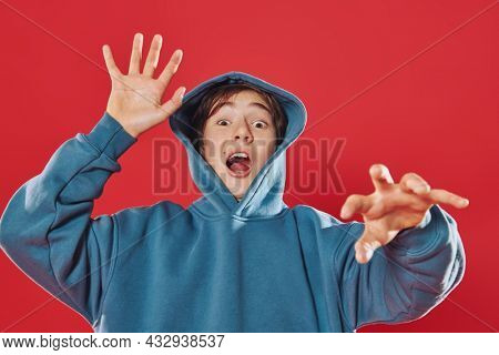 A teenage boy in a hoodie with a hood on his head scares. Studio portrait on a red background. Emotions of people. Horror, Halloween.