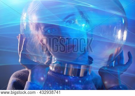 Portrait of a beautiful tender girl in a glass spacesuit surrounded by cosmic light. Space concept.