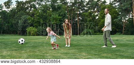 Little Girl Chasing The Ball. Young Family Playing Football On The Grass Field In The Park On A Summ
