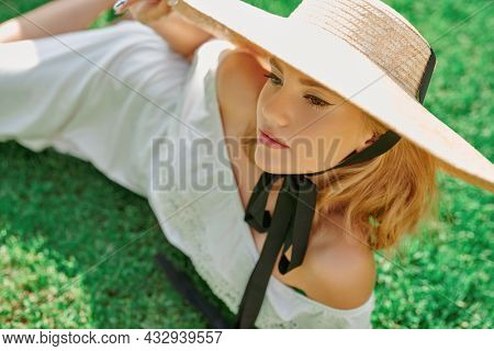 Summer beauty, fashion. Portrait of a romantic blonde girl in an elegant white dress and wide-brimmed straw hat, resting on a green lawn. Summer vacation.
