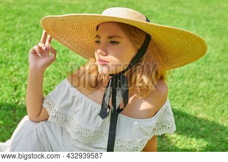 Portrait of a romantic blonde girl in an elegant white dress and wide-brimmed straw hat, resting on a green lawn. Summer vacation. Summer beauty, fashion.