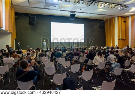 Moscow - April 26, 2021: Businesspeople sitting in chairs and listening to male speaker standing on stage with blank white screen during business conference in modern convention center