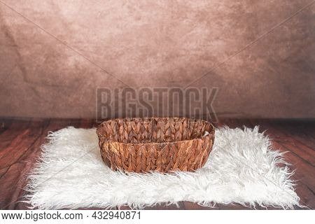Wicker Basket Lying On A Fuzzy Carpet Ready To Be Filled For Photograph Scene.