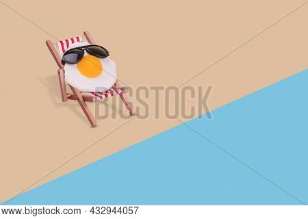 Creative Funny Composition Made Of Fried Egg With Sunglasses Sitting On Deck Chair On The Beach.