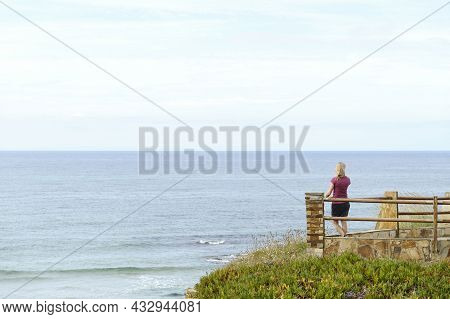 Rear View Of A Woman Contemplating The Sea From A Lookout Point.