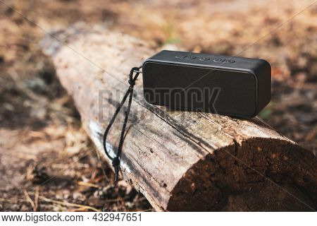 Portable Wireless Bluetooth Speaker For Listening To Music On A Log In The Forest.