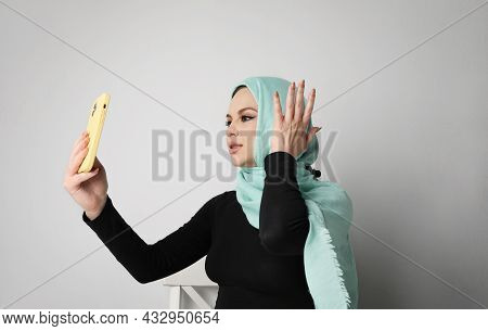 Young Arabian Woman With Happy Smile Using Smartphone, Isolated On White Wall.
