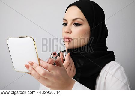Close-up Of Arabian Young Woman Doing Her Make-up, Isolated On White Wall.