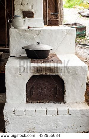 Ancient Bleached Stove With Large Metal Pot Ceramic Teapot And Old Iron In Country House Yard On Sum