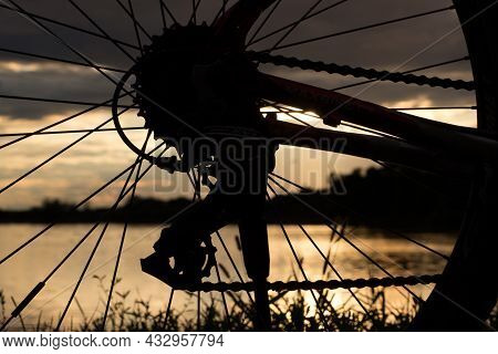 View Through A Bicycle Wheel With Derailleur And Chain On The Reflection Of The Setting Sun In The L