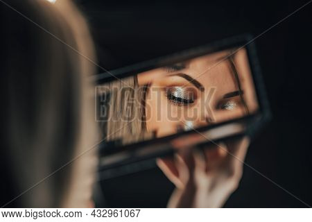 Reflection In Mirror Of Womans Eyes With Shinning Make-up. Young Lady Looks At Herself. Makeup At Ni