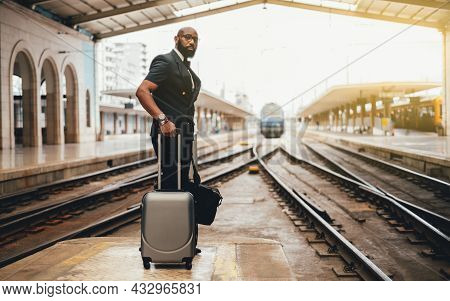 A Fashionable African Man Entrepreneur In Glasses Standing With Bags On The Railroad Platform Of A D