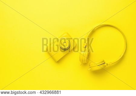 Yellow Camera And Yellow Headphones On A Yellow Background. Monochrome Image Of Creative Accessories