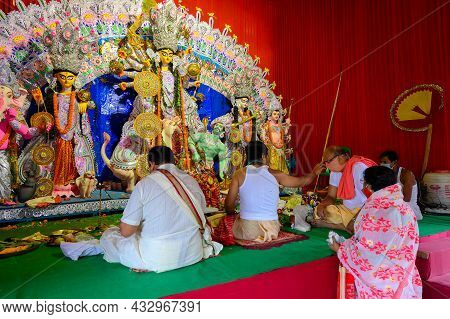 Howrah, West Bengal, India - 25th October 2020 : Hindu Purohit Putting Tilak On Masked Hindu Devotee
