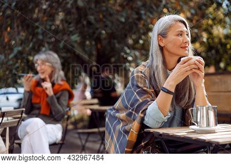 Senior Cafe Guests, Focus On Thoughtful Hoary Haired Mature Woman Holding Cup At Table