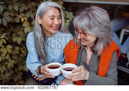 Happy Senior Asian Woman With Grey Haired Friend Clink Cups Sitting On Near Cafe Outdoors