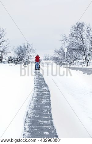 A Man In Red Winter Clothes Cleaning Snow By Using A Snowblower At The Long Walkway In Bright Day An