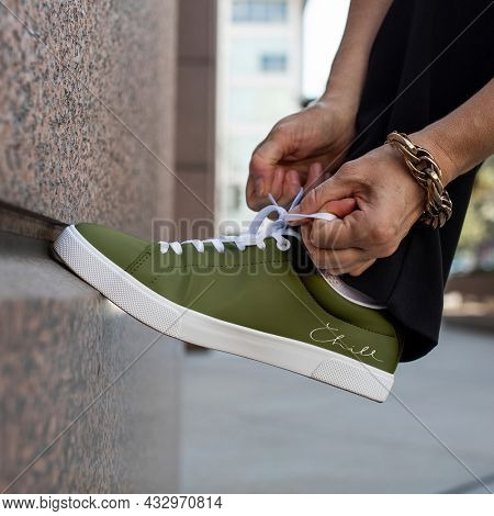 Canvas sneakers green model tying shoelaces apparel