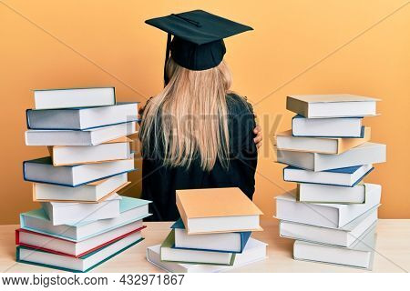 Young caucasian woman wearing graduation ceremony robe sitting on the table hugging oneself happy and positive from backwards. self love and self care
