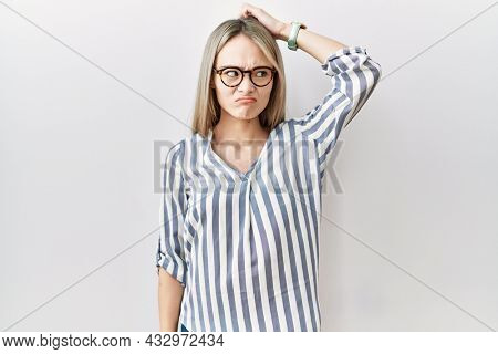 Asian young woman wearing casual clothes and glasses confuse and wonder about question. uncertain with doubt, thinking with hand on head. pensive concept.