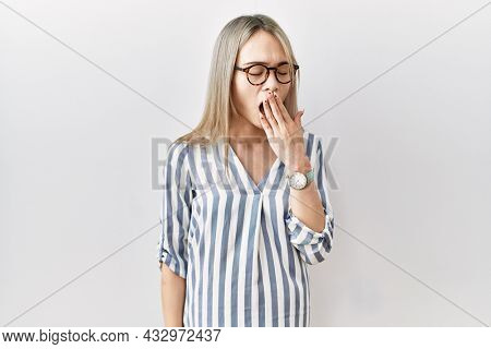 Asian young woman wearing casual clothes and glasses bored yawning tired covering mouth with hand. restless and sleepiness.