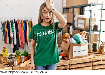 Asian young woman wearing volunteer t shirt at donations stand surprised with hand on head for mistake, remember error. forgot, bad memory concept.