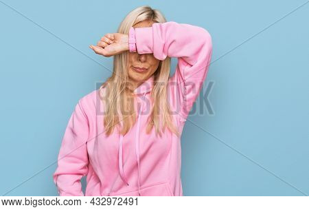 Young blonde woman wearing casual sweatshirt covering eyes with arm, looking serious and sad. sightless, hiding and rejection concept