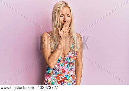 Young blonde woman wearing swimsuit bored yawning tired covering mouth with hand. restless and sleepiness.