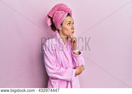 Young blonde woman wearing shower towel cap and bathrobe thinking worried about a question, concerned and nervous with hand on chin