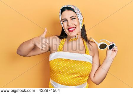 Young hispanic woman wearing pin up style smiling happy and positive, thumb up doing excellent and approval sign