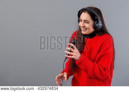 Young, Emotional Brunette With Headphones And A Microphone Dressed In A Red Sweater Sings Karaoke, I