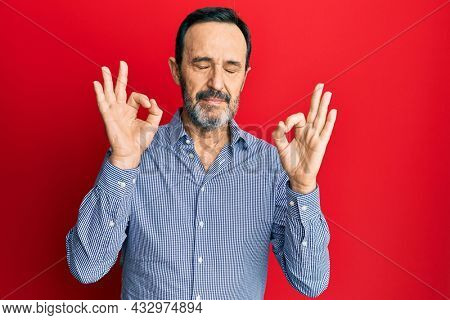 Middle age hispanic man wearing casual clothes relax and smiling with eyes closed doing meditation gesture with fingers. yoga concept.