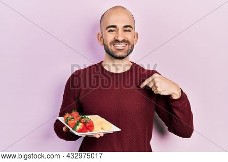 Young bald man eating fresh and healthy fruits pointing finger to one self smiling happy and proud