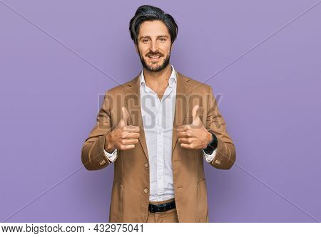 Young hispanic man wearing business clothes success sign doing positive gesture with hand, thumbs up smiling and happy. cheerful expression and winner gesture.