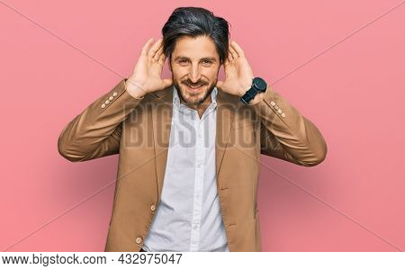 Young hispanic man wearing business clothes trying to hear both hands on ear gesture, curious for gossip. hearing problem, deaf