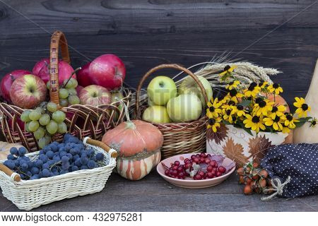 On A Dark Background, There Are Baskets With Red And Yellow Apples, A Bouquet Of Yellow Flowers, Ear