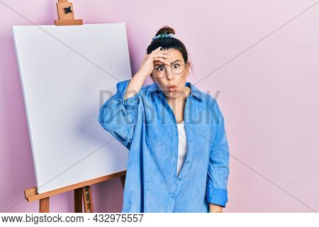 Young hispanic woman standing by painter easel stand worried and stressed about a problem with hand on forehead, nervous and anxious for crisis
