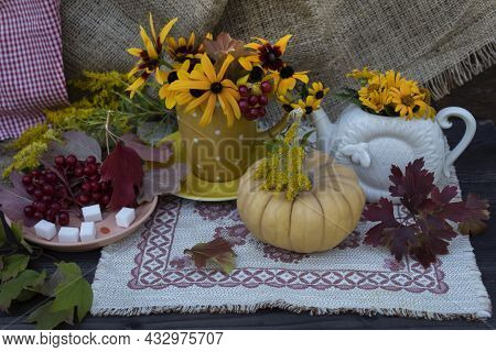 There Is A Teapot With Yellow Flowers On A Napkin, A Cup On A Saucer With Flowers, A Saucer With Vib