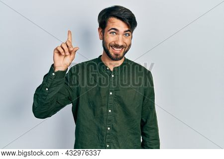 Young hispanic man wearing casual clothes smiling with an idea or question pointing finger up with happy face, number one