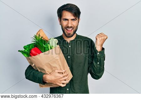 Young hispanic man holding paper bag with bread and groceries screaming proud, celebrating victory and success very excited with raised arms
