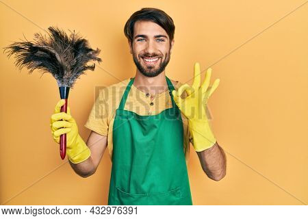 Young hispanic man wearing apron holding cleaning duster doing ok sign with fingers, smiling friendly gesturing excellent symbol