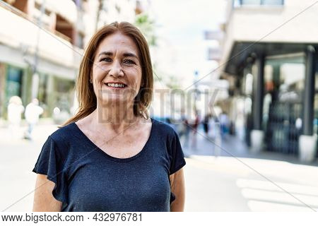 Middle age hispanic woman smiling happy outdoors on a sunny day