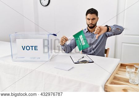 Young handsome man with beard at political campaign election holding arabia saudita flag with angry face, negative sign showing dislike with thumbs down, rejection concept