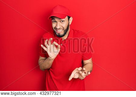 Hispanic man with beard wearing delivery uniform and cap disgusted expression, displeased and fearful doing disgust face because aversion reaction.