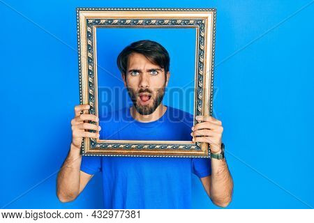 Young hispanic man holding empty frame afraid and shocked with surprise and amazed expression, fear and excited face.