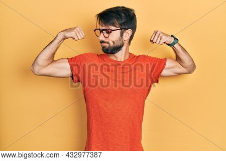 Young hispanic man wearing casual clothes and glasses showing arms muscles smiling proud. fitness concept.