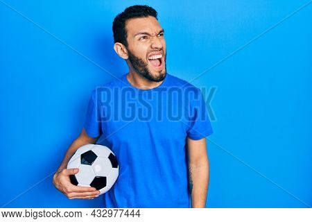 Hispanic man with beard holding soccer ball angry and mad screaming frustrated and furious, shouting with anger. rage and aggressive concept.